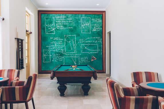 salón con mesa de billar y pizarra verde