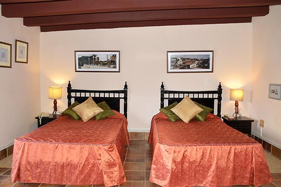 habitación con dos camas de madera colonial