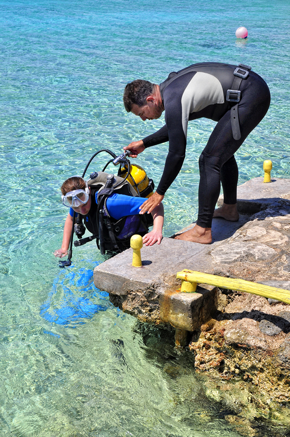 diving instructor helping tourist