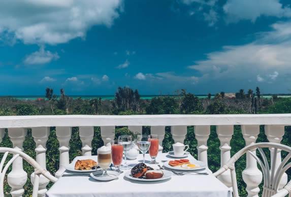 balcón con mesa con desayuno y vista al mar