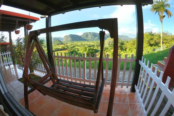balcón con columpio de madera y vista a la montaña