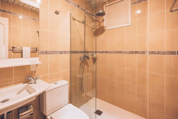 bathroom with shower and white furniture