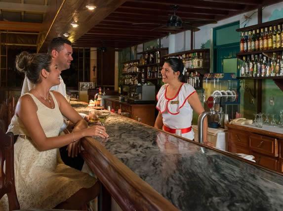 clientes en la barra de mármol del bar