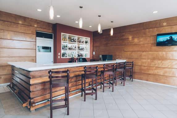 barra de madera y mármol con banquetas de madera