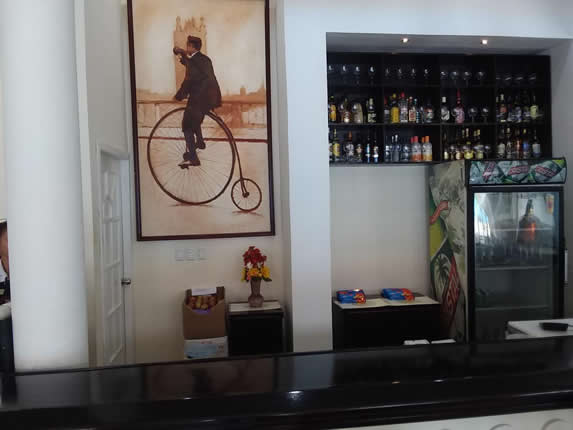 wooden bar and bottles on a shelf in the back