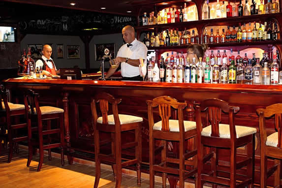 bar with wooden furniture and bottles on shelfs