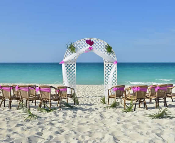 beach decorated with furniture and flowers for wed