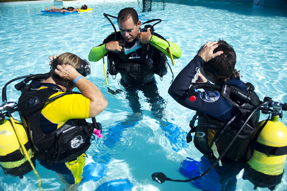teacher and tourists in diving suit in the pool