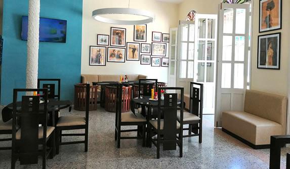 cafetería con mobiliario y cuadros decorativos