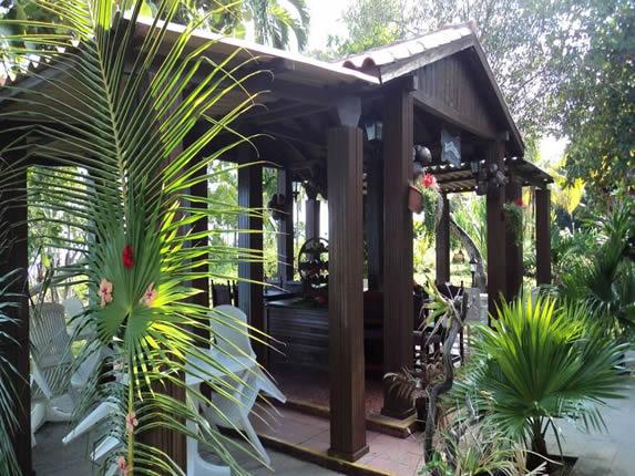 techo de madera y teja en el jardín con mobiliario