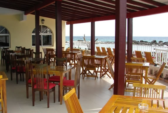 tables and chairs facing the sea under wooden roof