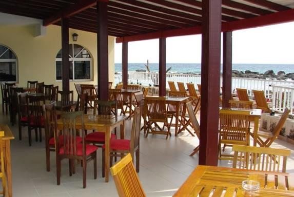 mesas y sillas frente al mar bajo techo de madera
