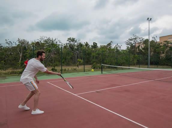 turista jugando tenis en las canchas