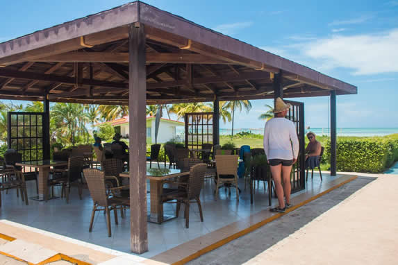 tables under wooden roof by the sea