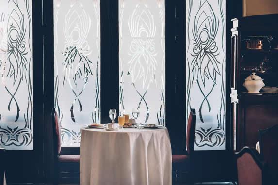 mesa servida y ventanal con vitral al fondo