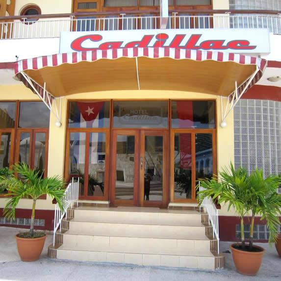 entrada del hotel con puertas de madera y cartel