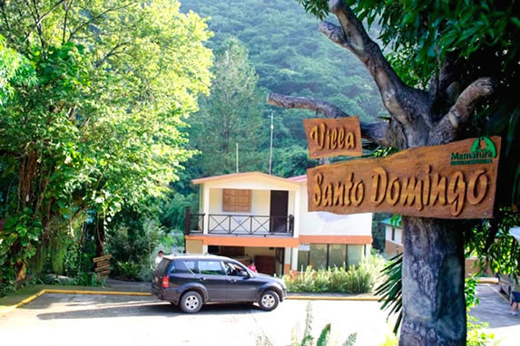 hotel entrance with wooden sign on a tree