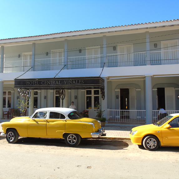 colonial facade and vintage cars parked outside