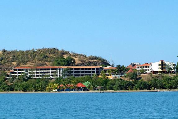 vista del hotel desde el mar con montañas atrás