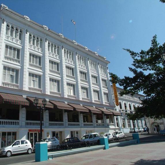 Fachada blanca del hotel bajo el cielo azul