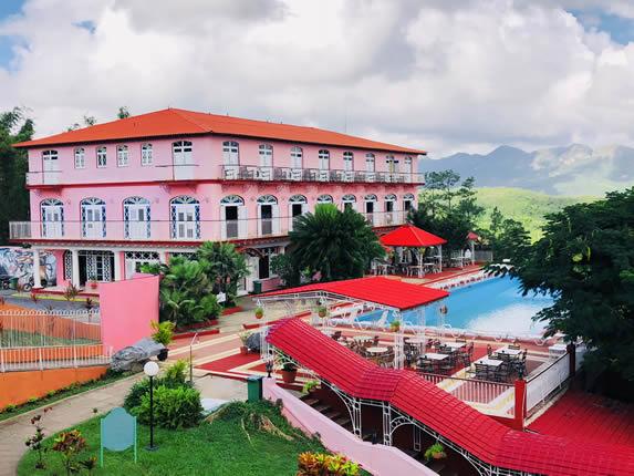 fachada del hotel rodeado de montañas y vegetación
