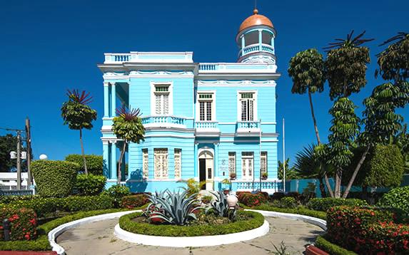 blue hotel facade with garden in front