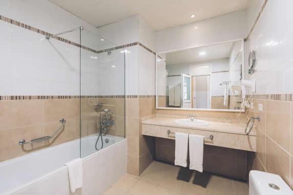 baño de mármol con tina y espejos