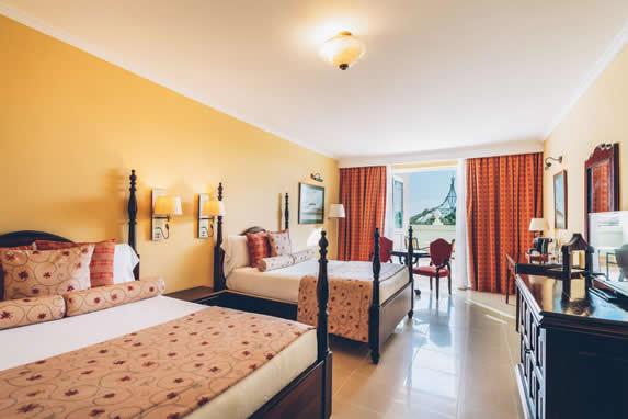 habitación con dos camas de madera y balcón
