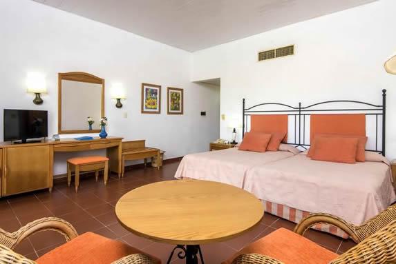 habitación con dos camas y mobiliario de madera