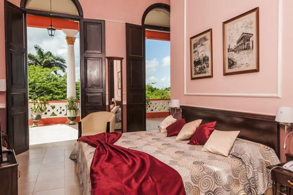 habitación de una cama con balcón y vegetación