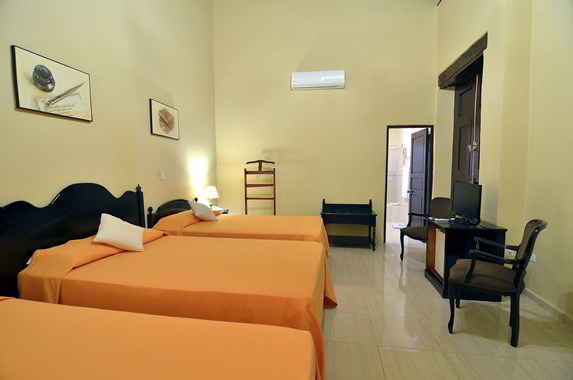 habitación de tres camas con mobiliario de madera