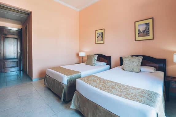 habitación de dos camas con mobiliario de madera