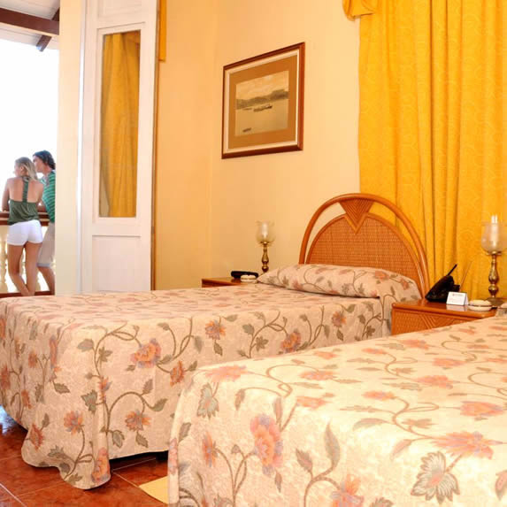 habitación de dos camas con mobiliario de mimbre