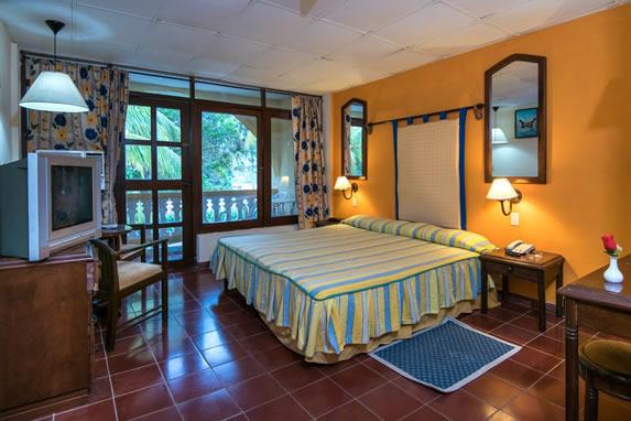 habitación de una cama con mobiliario y balcón