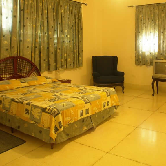 habitación de una cama con mobiliario y cortinas