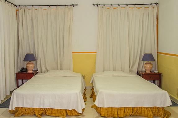 habitación de dos camas con mobiliario y cortinas
