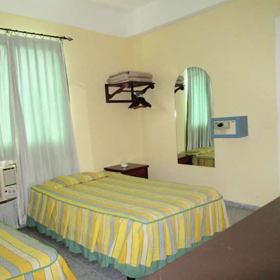habitación de dos camas con espejo y cortinas