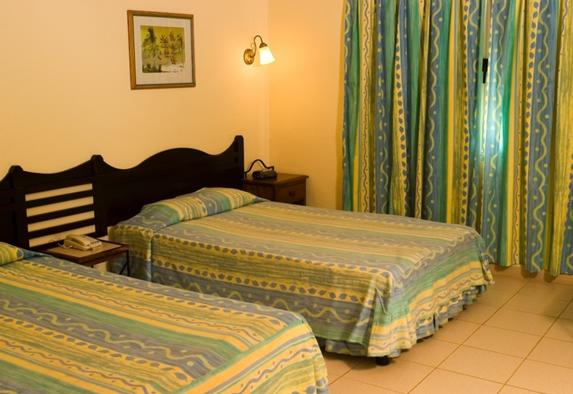 habitación de dos camas con cortina y mobiliario