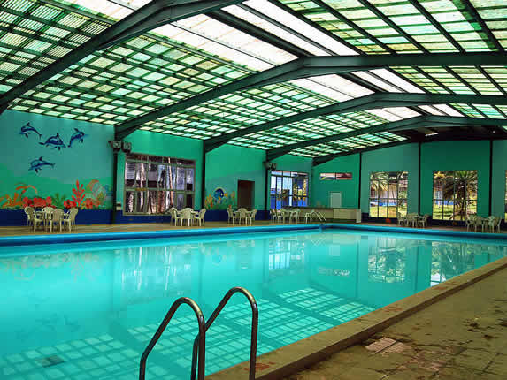 indoor pool with plastic tables and chairs