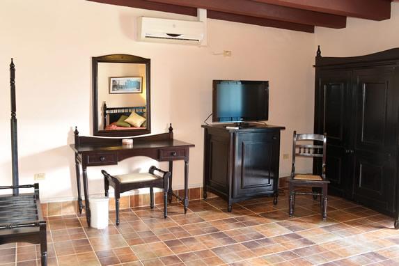 habitación con televisor y mobiliario de madera