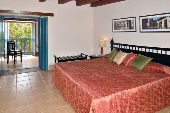 habitación colonial con cama grande y balcón