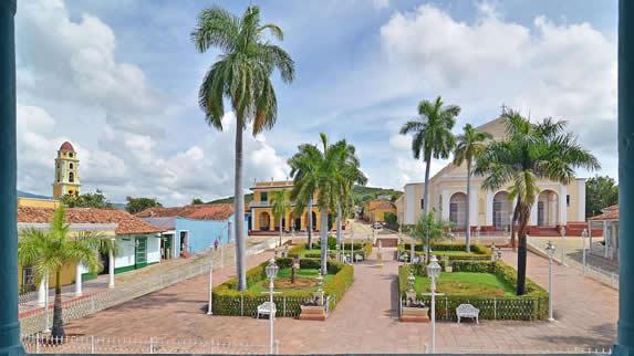 parque colonial con edificios coloridos y árboles