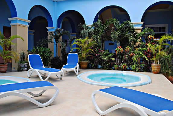 Jacuzzi with sun beds and plants around