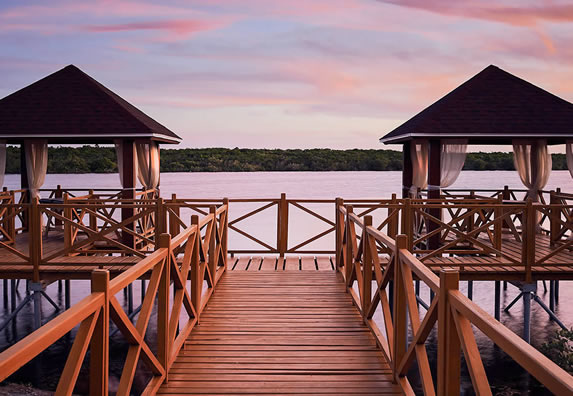 wooden pier over the lagoon at sunset