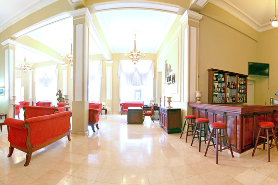 lobby with red furniture and wooden bar