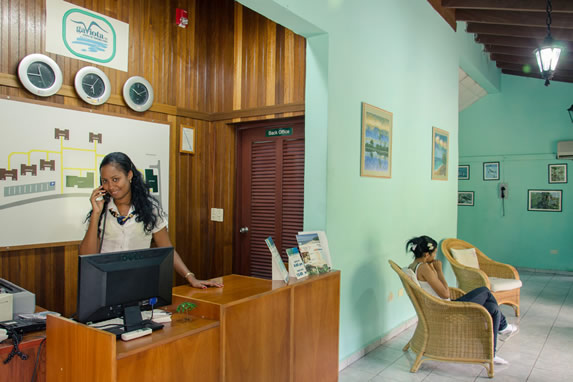 recepcionista en el lobby con buró de madera