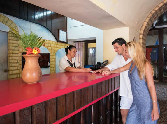 turistas en el buró de recepción del hotel