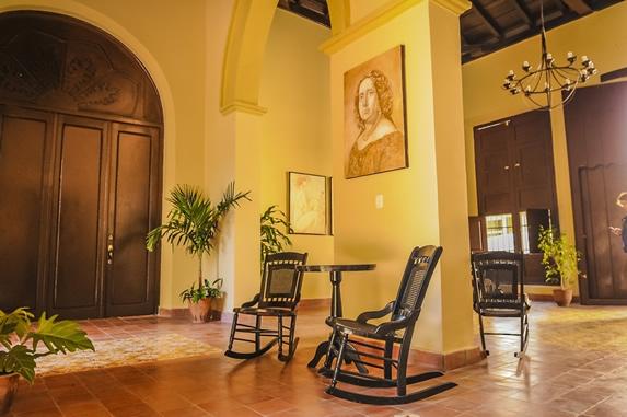 lobby con sillones de madera y cuadros decorativos