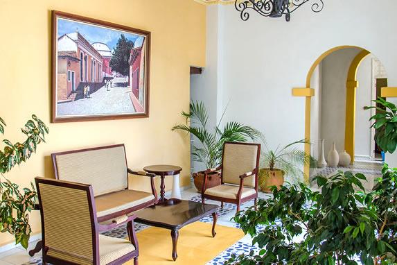lobby con plantas y mobiliario de mimbre