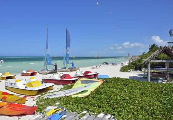 playa con bicicletas acuáticas y catamaranes